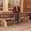 File: Dr Leonard Lawley - Len Lawley on a bicycle in front of the Kingston Polytechnic sign