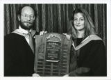 Law Reunion blue folder - Two students holding Louis M. Brown award plaque