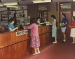 File: Kingston Polytechnic Photographs 1960s onwards - Library staff (Kingston Hill) - includes Angela Horrocks behind lending desk and Bertrand Daldy in the queue